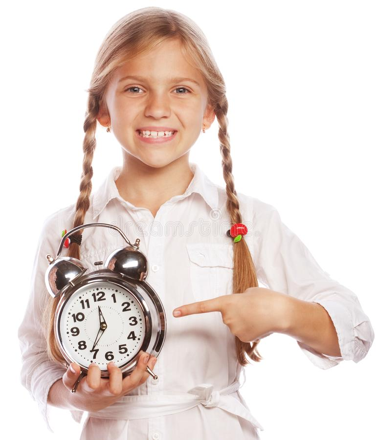 Image of cheerful little girl child standing isolated over white background. Looking camera pointing to clock alarm. stock photos
