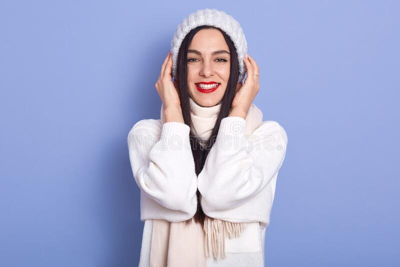 Image of cheerful magnetic good looking young female looking directly at camera, wearing white sweater, scarf and hat, putting stock photo