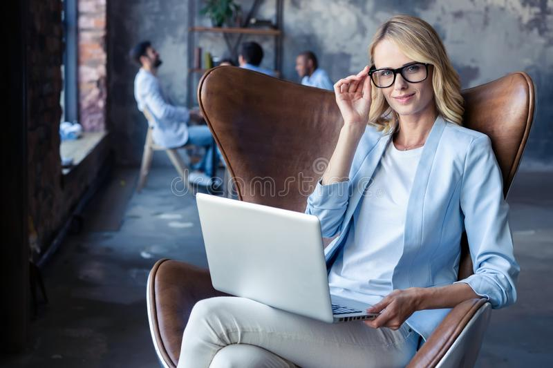 Image of cheerful office woman with blond hair in business wear sitting on chair and working with laptop office. stock image