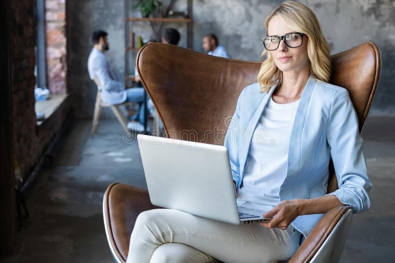 Image of cheerful office woman with blond hair in business wear sitting on chair and working with laptop office. royalty free stock image