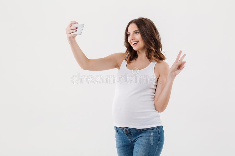 Cheerful pregnant woman make selfie with her belly royalty free stock photo