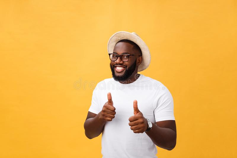Image of cheerful young african man standing and posing over yellow background with thumbs up. Looking at camera royalty free stock photo