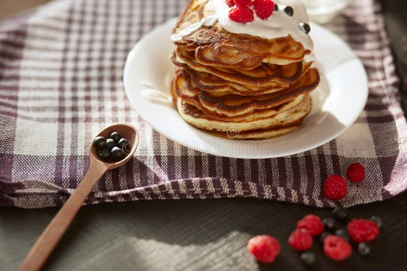 Image of cheese pancakes with sour cream and fresh berries, blackberry jam in wooden spoon, whipped cream on muffins top, served royalty free stock photography