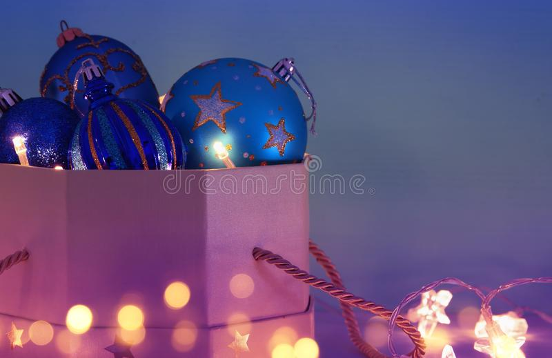 Image of christmas festive tree blue, purple and violet balls decoration in the gift box. royalty free stock image