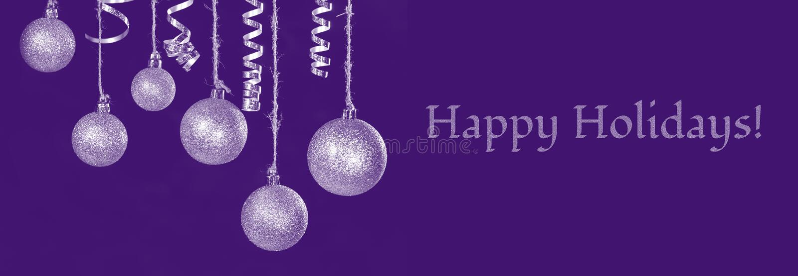 Image of christmas festive tree gold ball decoration in front of black background There is the text Happy Holidays. Image of christmas festive tree gold ball stock photo