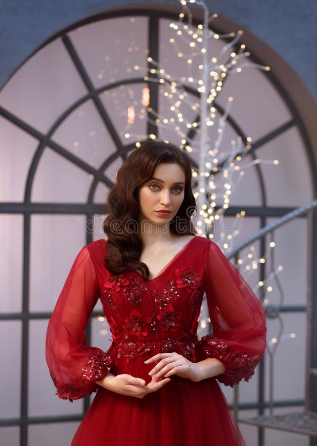 Image of a Christmas witch, a delightful red dress adorned with flowers and sleeves, a girl with warm wavy hair, a New royalty free stock photo