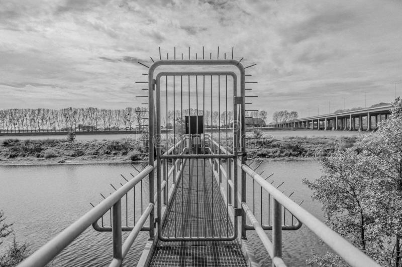 Image of a closed door prohibiting passage on a bridge near the river Maas. With in the background the highway to Antwerp Belgium, between Elsloo and Meers royalty free stock photography