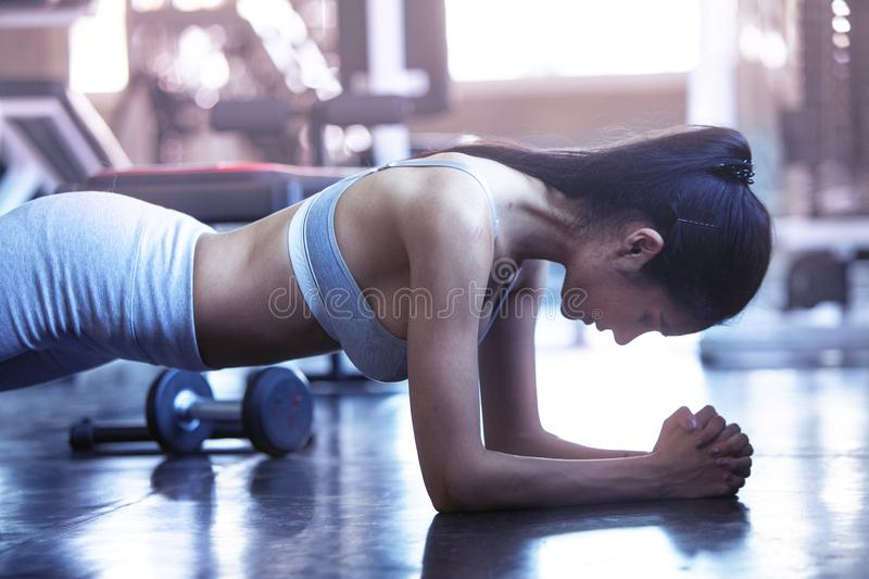 Closed up sporty athlete planking in gym royalty free stock image
