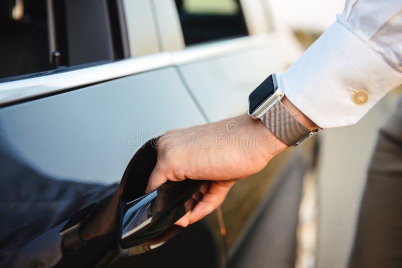 Image closeup of caucasian man wearing wrist watch, opening door. Image closeup of caucasian man wearing wrist watch opening door of luxury black car royalty free stock photo