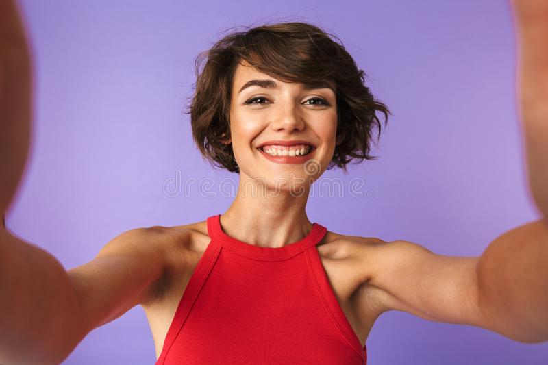 Image closeup of european charming woman 20s in casual wear smiling and taking selfie, isolated over violet background royalty free stock photo