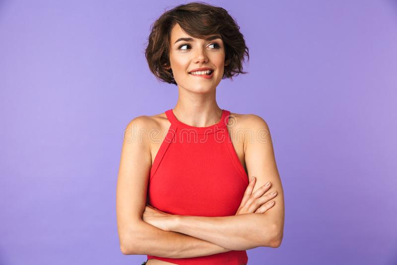 Image closeup of pretty brunette woman 20s in casual wear smiling while standing with arms crossed, isolated over violet royalty free stock photography
