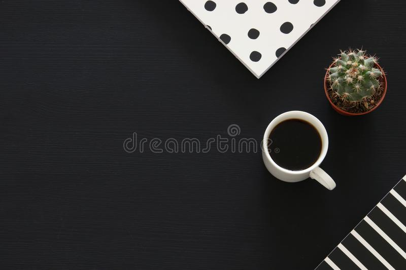 image of coffee cup and notebook over black background. Top view. royalty free stock photo