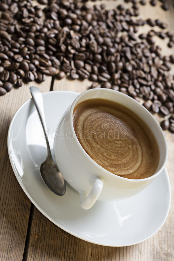 Image of a coffee cup and saucer with an old vintage spoon on a wooden table top. surrounded by raw coffee beans, taken at an royalty free stock photography