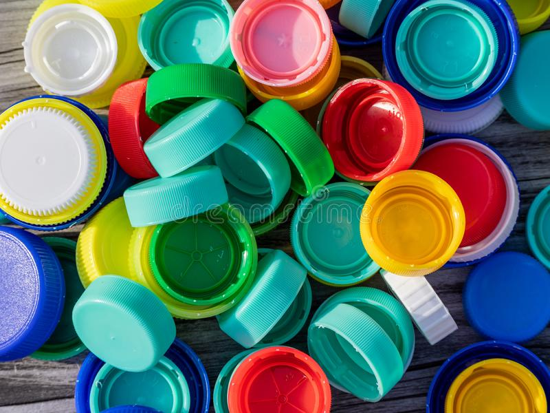 Image of colorful plastic caps on a wooden table. With blurry background royalty free stock photos