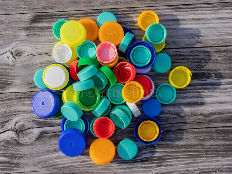 Image of colorful plastic caps on a wooden table. With blurry background stock photography