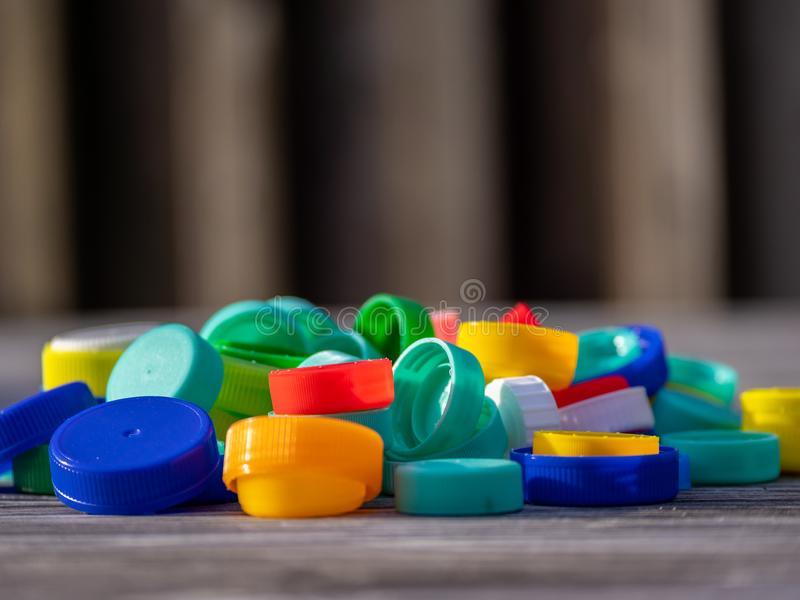 Image of colorful plastic caps on a wooden table. With blurry background royalty free stock photography