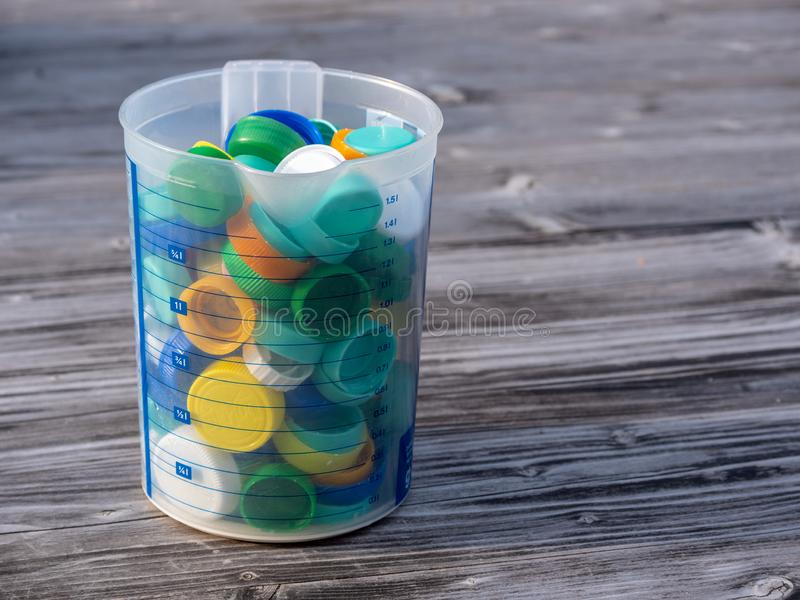 Image of colorful plastic caps on a wooden table. With blurry background royalty free stock photo