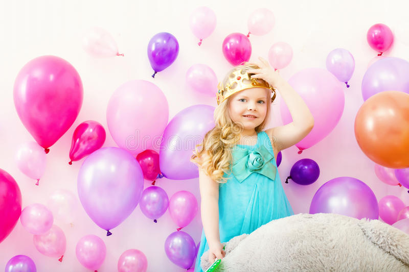 Image of comely little girl tries on toy crown. Studio shot of comely little girl tries on toy crown stock photo