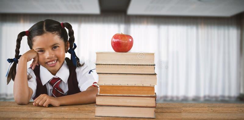 Image composée d'écolière se penchant par les livres et la pomme sur le bureau image libre de droits