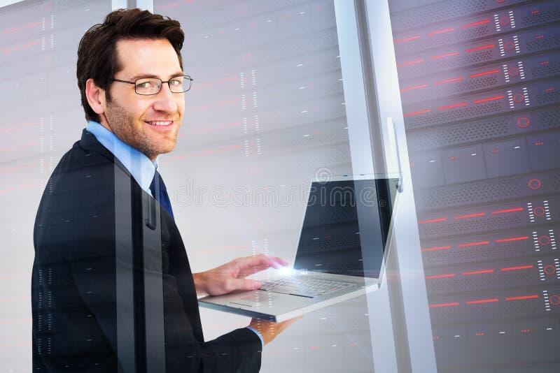 Image composée d'homme d'affaires de sourire utilisant un ordinateur portable image libre de droits