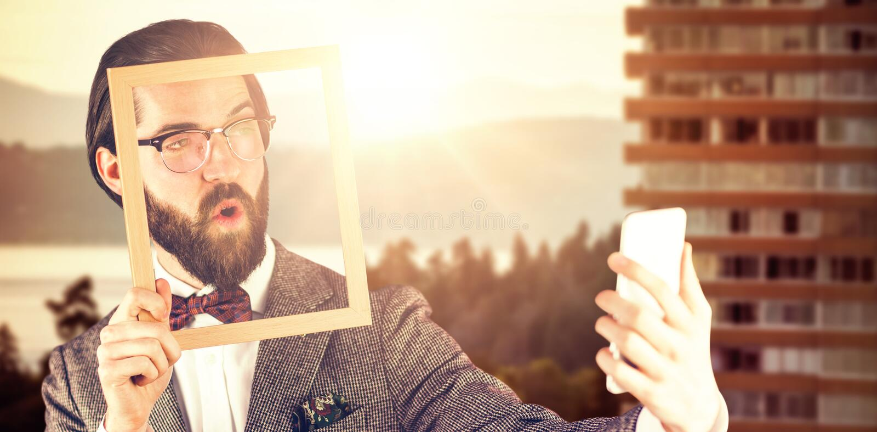 Image composée d'homme d'affaires prenant le selfie tout en tenant le cadre photographie stock