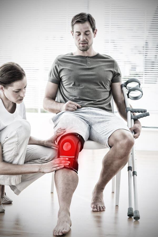 Image composée d'homme de examen de physiothérapeute avec des béquilles photographie stock
