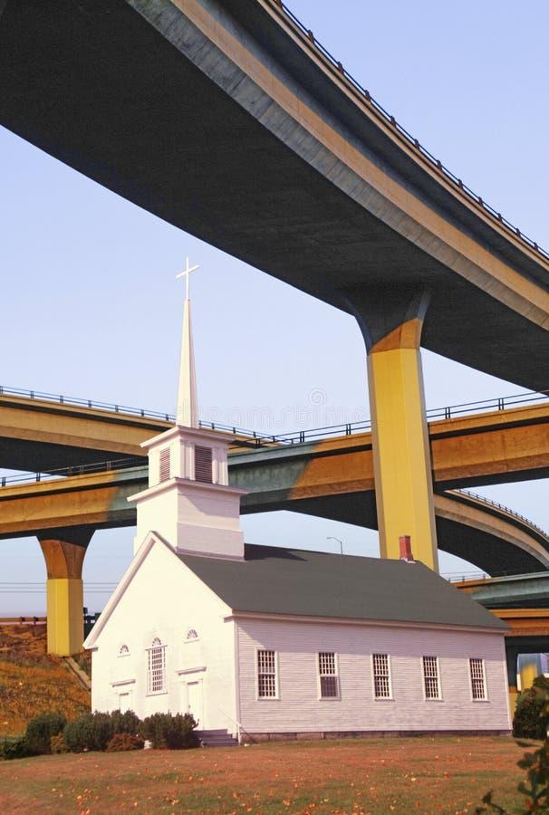 Image composée d'une église parmi des passages supérieurs d'autoroute photographie stock