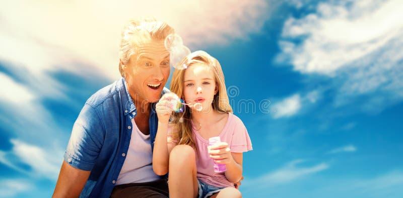 Image composée d'une petite des bulles de soufflement fille avec son père image libre de droits