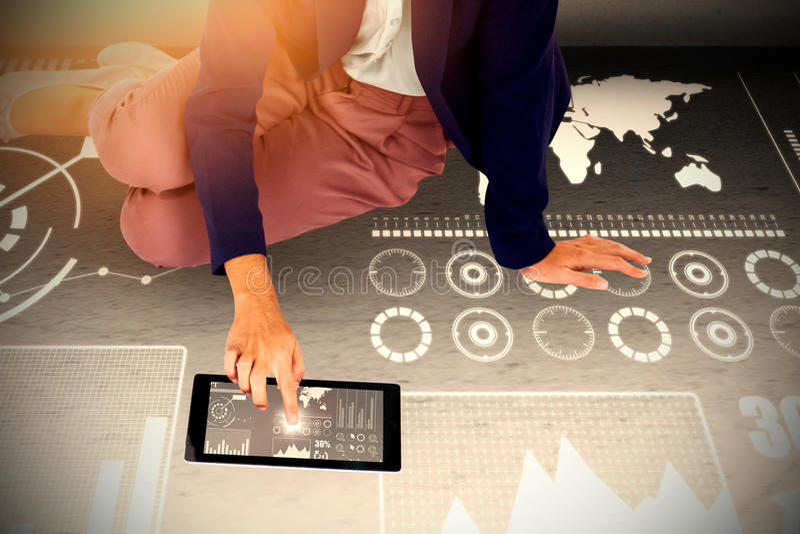 Image composée de basse section de la femme d'affaires à l'aide du comprimé numérique sur le fond blanc photographie stock libre de droits