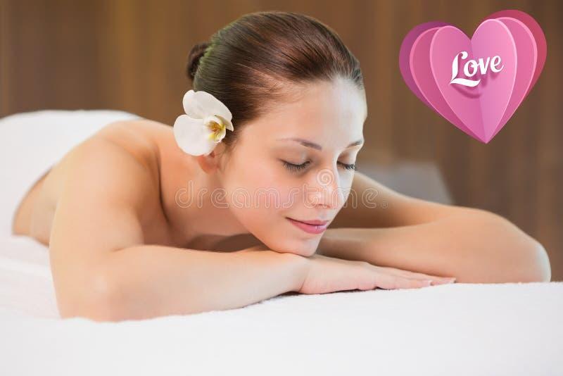 Image composée de belle femme se trouvant sur la table de massage au centre de station thermale photographie stock