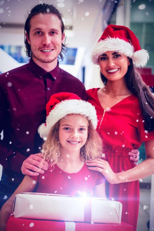 Image composée de famille dans le vêtement de Noël se tenant avec des cadeaux de Noël photos stock