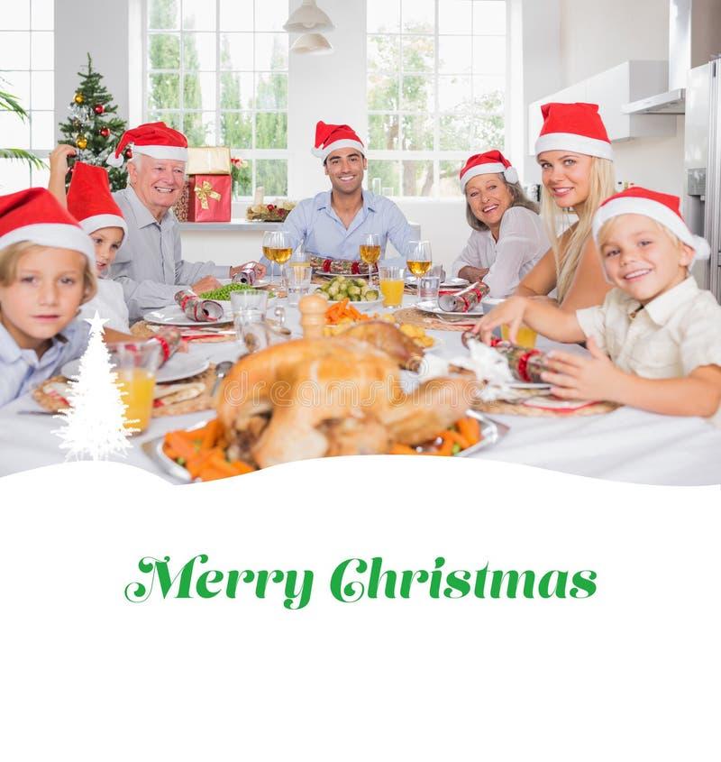 Image composée de famille de sourire autour de la table de dîner à Noël photo libre de droits