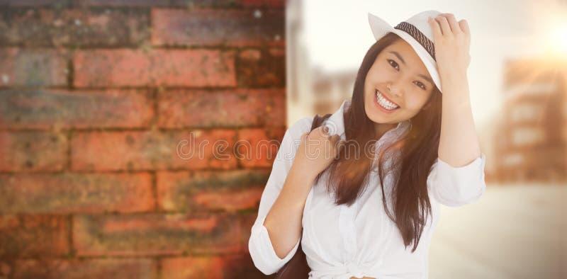 Image composée de femme avec les vêtements sport tenant son chapeau photographie stock libre de droits