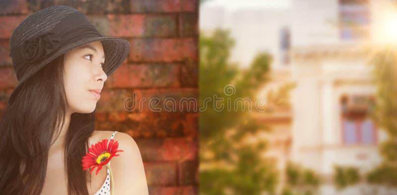 Image composée de femme gaie avec la fleur regardant loin utilisante un chapeau images libres de droits