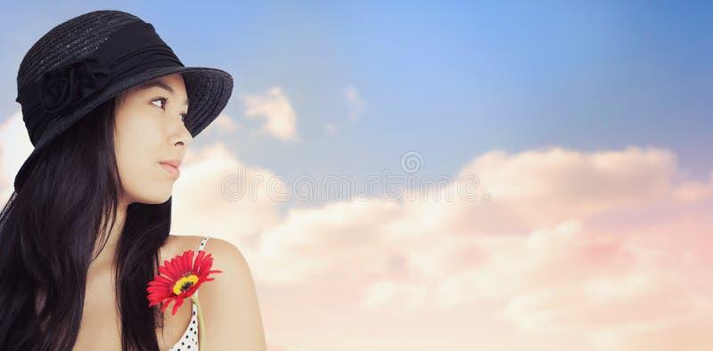 Image composée de femme gaie avec la fleur regardant loin utilisante un chapeau photos stock