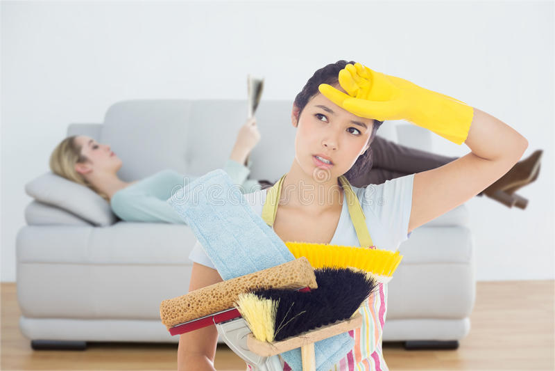 Image composée de femme lasse tenant des outils de nettoyage images libres de droits