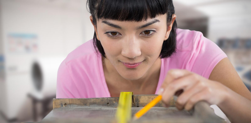 Image composée de femme mesurant la planche en bois avec le ruban métrique photographie stock libre de droits