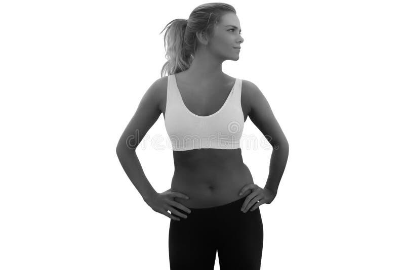 Image composée de femme modifiée la tonalité avec des mains sur des hanches sur la plage photo stock