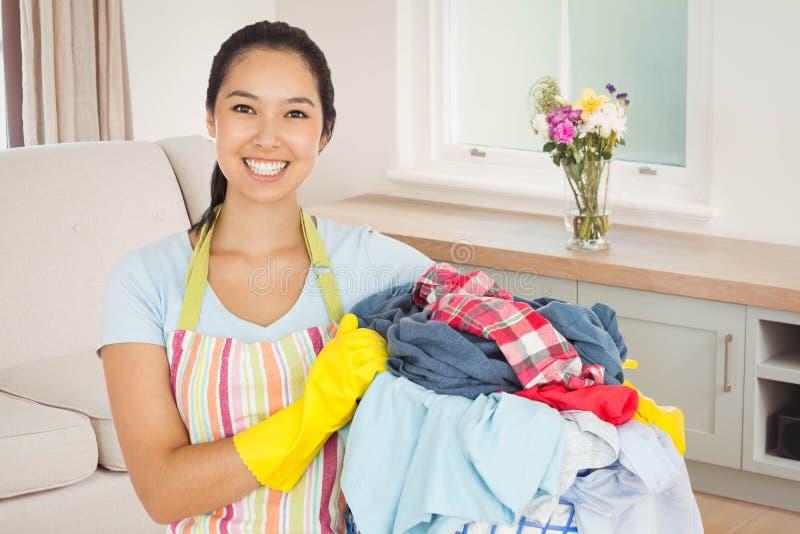 Image composée de femme riante tenant le panier de blanchisserie image stock
