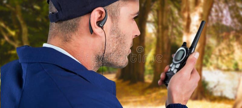 Image composée de fin de l'agent de sécurité parlant sur le talkie-walkie photo stock