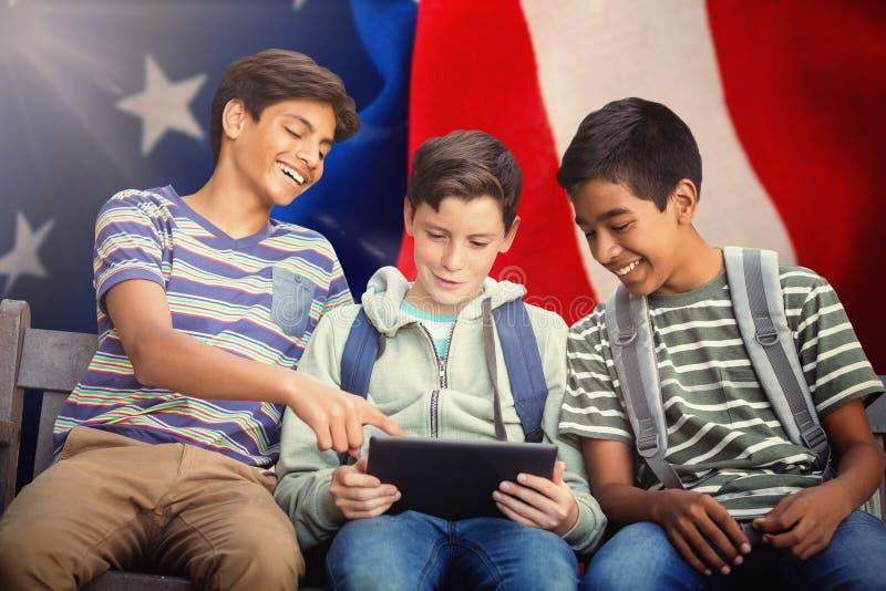 Image composée de garçon avec des amis à l'aide du comprimé numérique sur le banc photos libres de droits