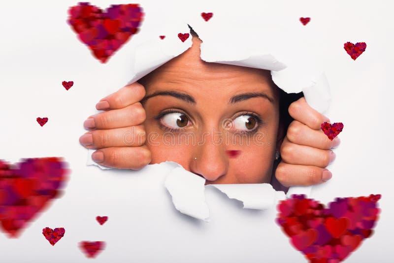 Image composée de jeune femme regardant par la déchirure de papier photographie stock libre de droits