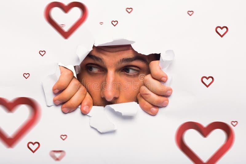 Image composée de jeune homme regardant par la déchirure de papier photos stock