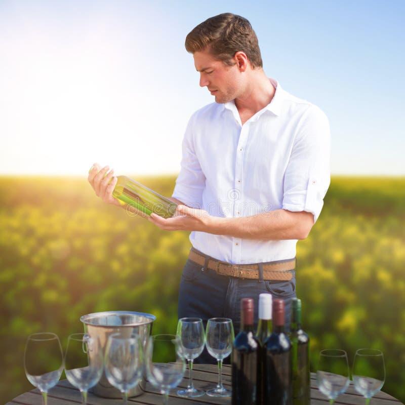 Image composée de jeune homme tenant la bouteille de vin par des verres sur le baril images libres de droits