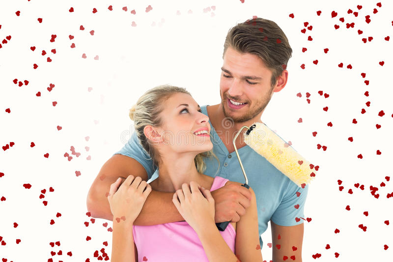 Image composée de jeunes couples étreignant et tenant le rouleau de peinture image libre de droits