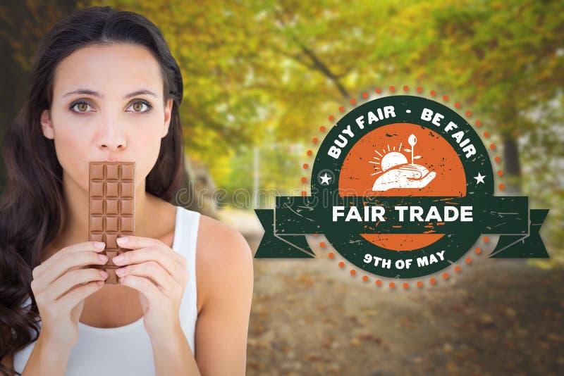 Image composée de jolie brune mangeant la barre du chocolat photos stock
