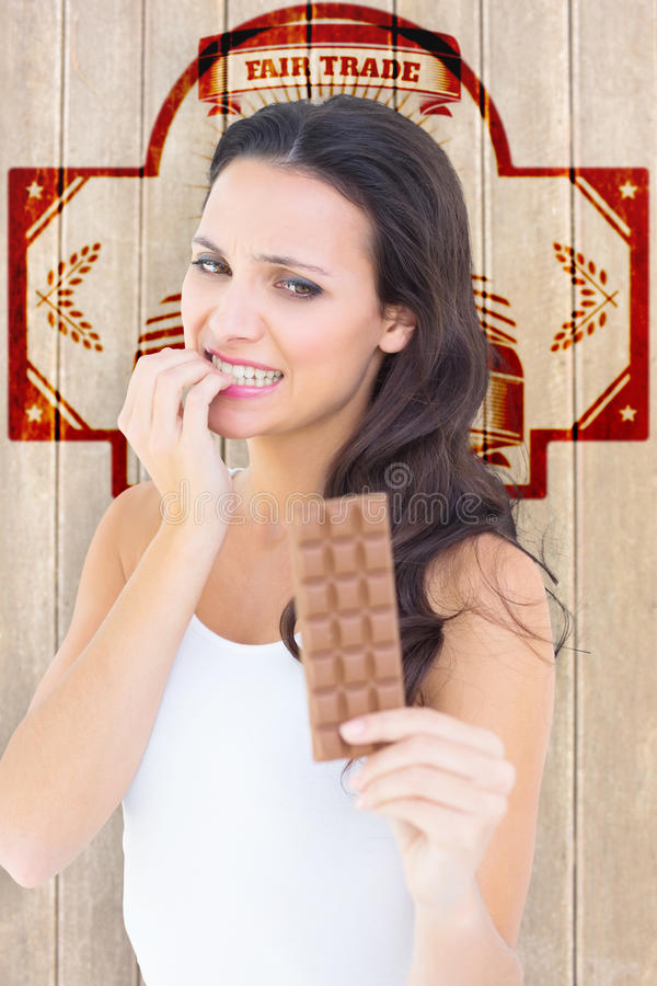 Image composée de jolie brune regardant craintivement le chocolat images libres de droits
