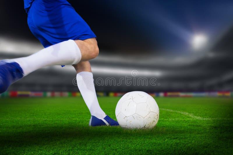 Image composée de joueur de football donnant un coup de pied la boule image libre de droits