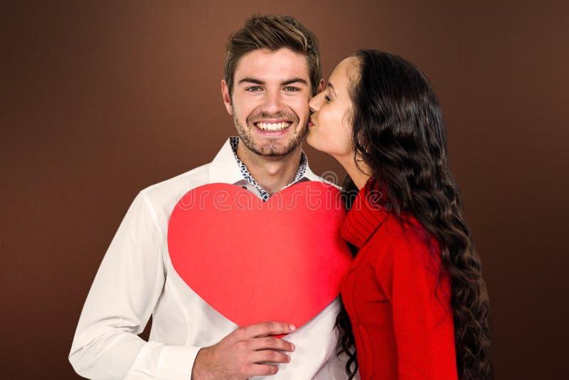 Image composée de l'homme tenant le coeur de papier et embrassé par l'amie photographie stock libre de droits