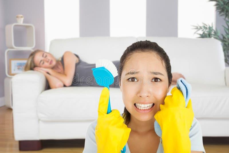 Image composée de la femme affligée tenant le tissu et la brosse de frottement photos stock